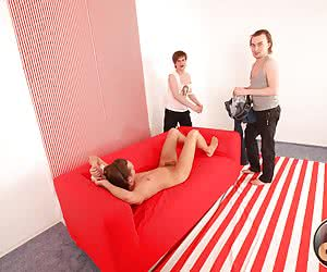 Handsome guy gets his tight ass double penetrated by two his friends on a new red sofa.