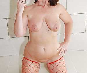 Manuela, horny mature milf slut dressed in red high heel shoes and fishnet stockings. Spreading her legs wide open and p