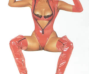 Passionate blonde pinup girl in high red boots and latex lingerie