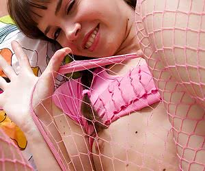 Playful young girl in net hose exposes her perky titties and delicious pussy