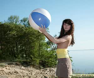 Busty young brunette playing in the nude on the sandy beach with a ball