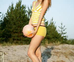 Redheaded young college girl having fun playing nude volleyball